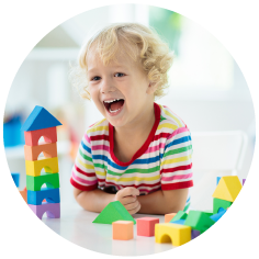 A child smiling and playing with brightly coloured blocks.